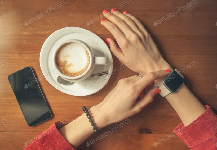 female hands using smart watch with blank screen with coffee