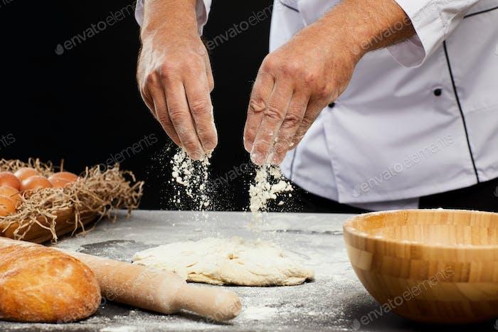 Chef Backen Brot vor schwarzem Hintergrund