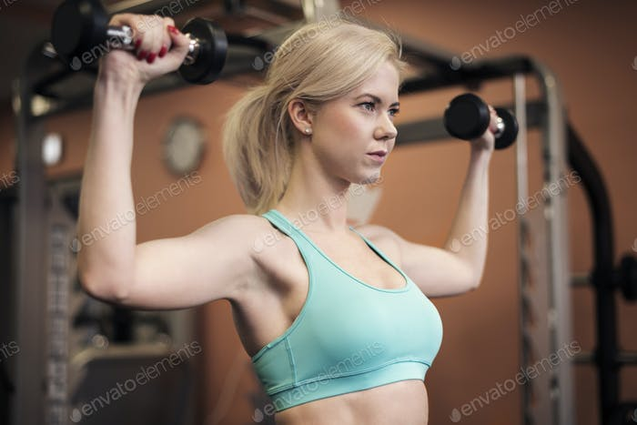 Woman shaping her shoulders at the gym