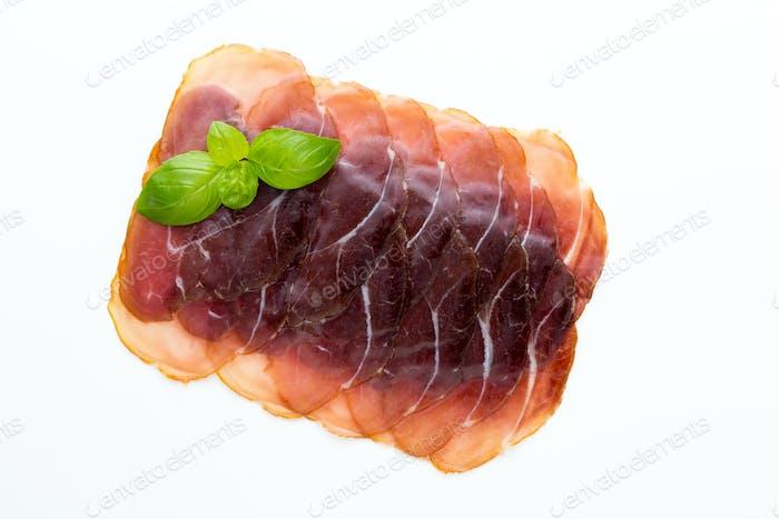 Italian prosciutto crudo or jamon. Raw ham. Isolated on white background