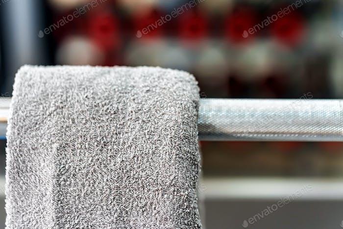 Grey towel hangs on barbell in gym