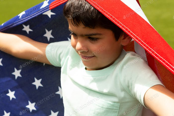 Schoolboy standing with an American flag on his head and his shoulders
