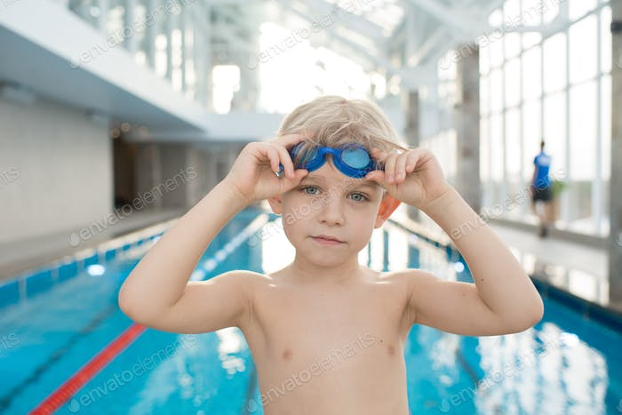 Serious confident swimmer putting on goggles