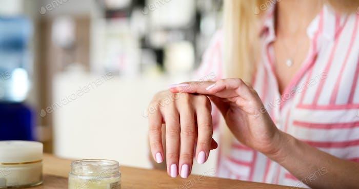 Frau Anwendung Feuchtigkeitscreme auf die Hände