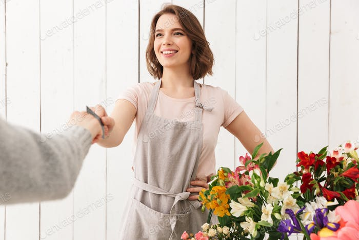 Florist lady standing with flowers in workshop with buyer.