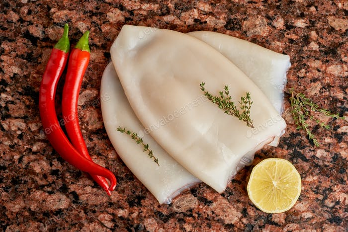 Three carcasses of fresh raw squid with lemon, pepper, thyme on a marble stone dark table.