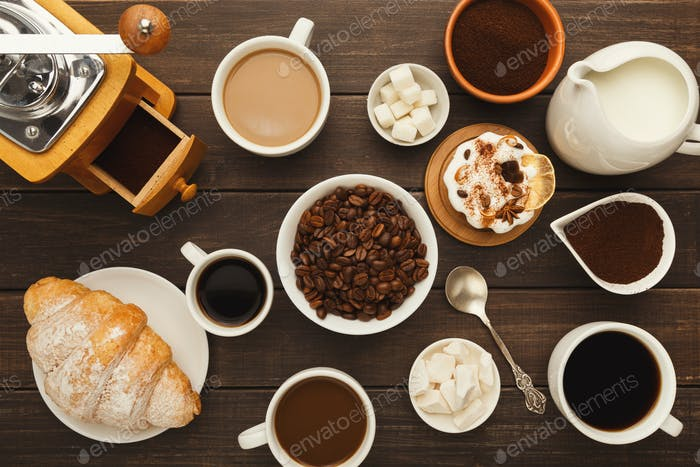 Various coffee cups and sweet pastry on vintage wooden table, top view