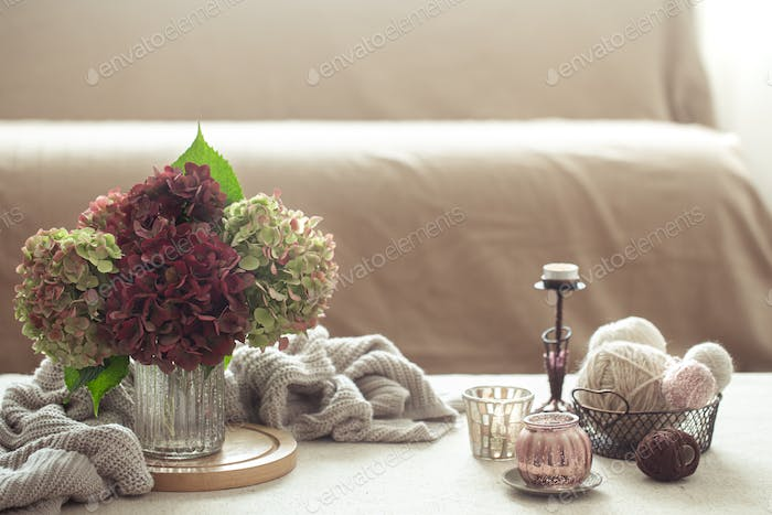Autumn floral arrangement with hydrangea and home decor details. Autumn home comfort concept.