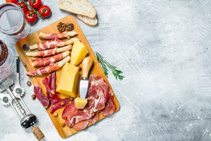 Antipasto background. Various meat and cheese snacks with red wine.