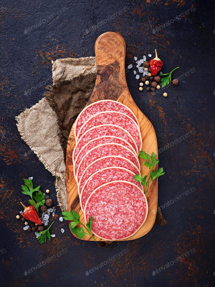 Italian salami sausage on wooden board.