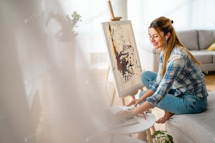 Art, creativity, hobby, job and creative occupation concept. Woman painting at home
