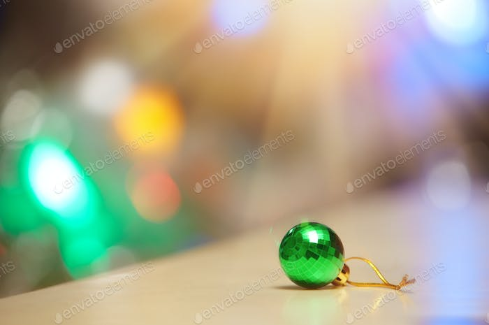 Green Christmas ball and illuminated background