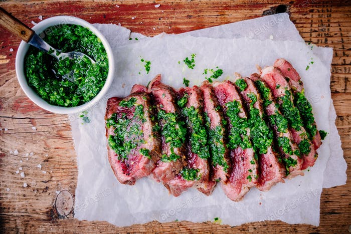 Sliced grilled barbecue beef steak with green chimichurri sauce