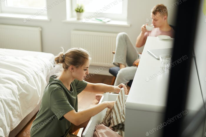 Young female taking clothes out of chest of drawers