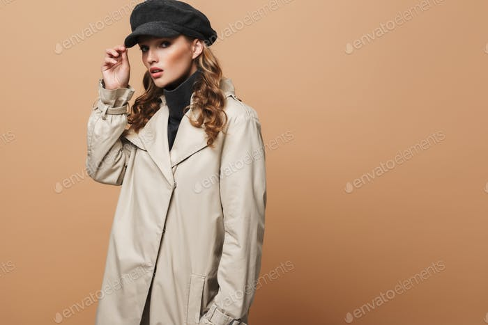 Young beautiful woman with wavy hair in classic trench coat and cap thoughtfully looking in camera
