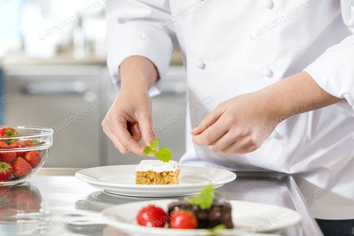 Chef decorate dessert cake with lemon leaf