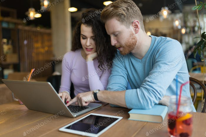 Happy couple spending time at coffee shop working on laptop
