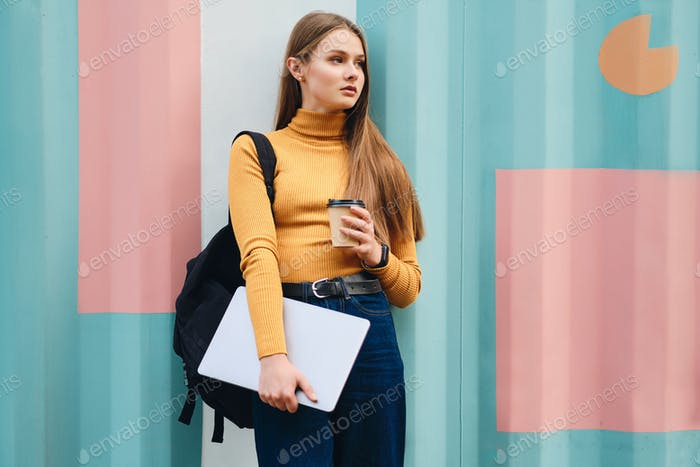 Attractive serious student girl with laptop and coffee to go looking away over colorful background