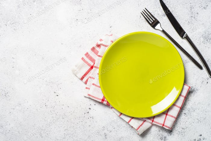 Green plate, cutlery and tablecloth on light stone table