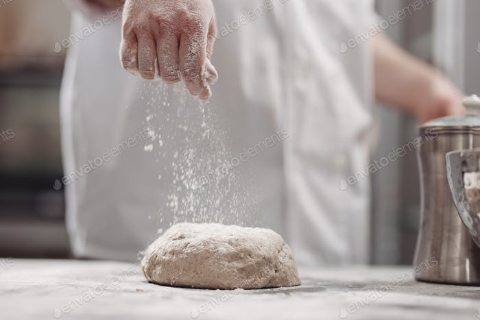 Baker adds flour to dough on the table in the bakery