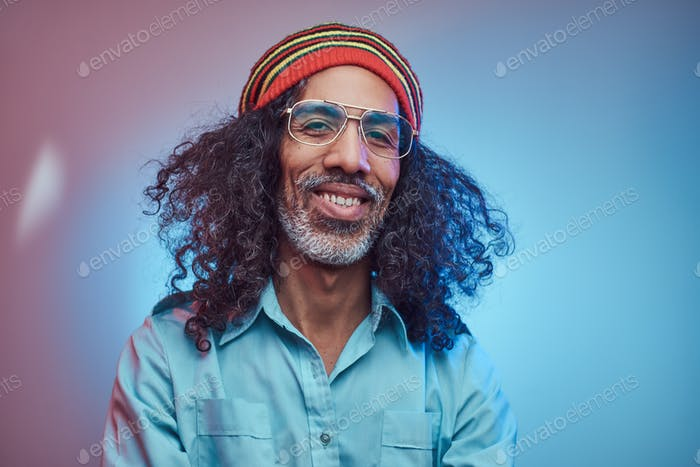 Studio portrait of African Rastafarian male wearing a blue shirt and beanie.