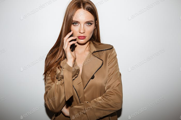 Beautiful lady in trench coat standing and thoughtfully looking in camera talking on her cellphone