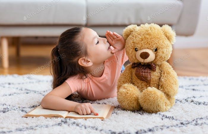 Little Asian Girl Whispering Sharing Secret mit Teddybär drinnen