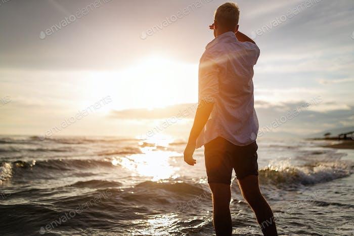 Young man enjoying sunset on summer vacation