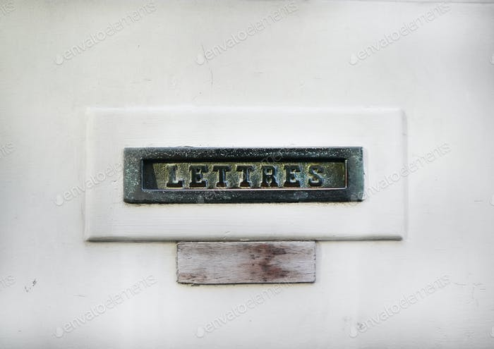 Vintage mail slot in a white door