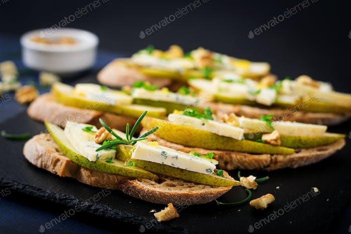 Bruschetta Sandwich mit Birne, Blauschimmelkäse, Honig und Nuss auf dunklem Hintergrund.