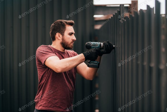 Working man portrait - construction worker using screwdriver and installing metal fence elements
