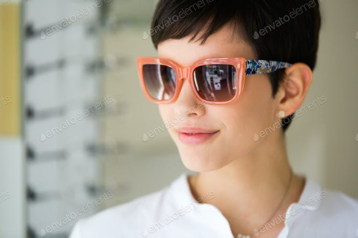 Young beautiful woman at optician with glasses buying sunglasses
