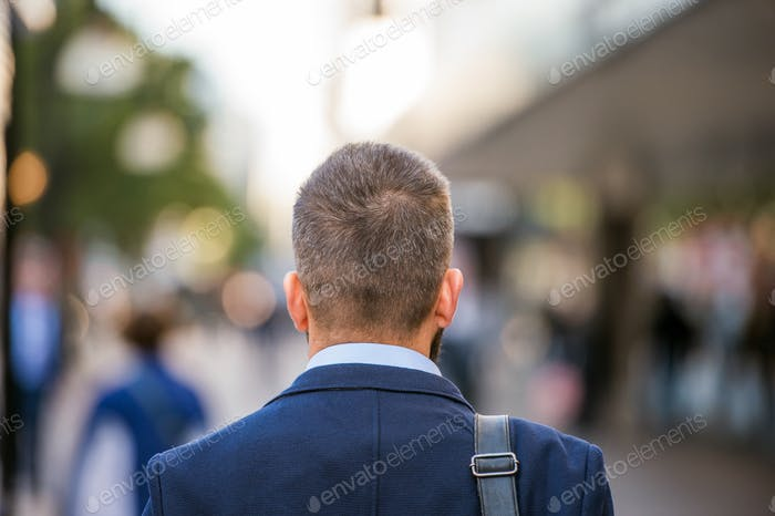 Unrecognizable manager walking in the street, rear view
