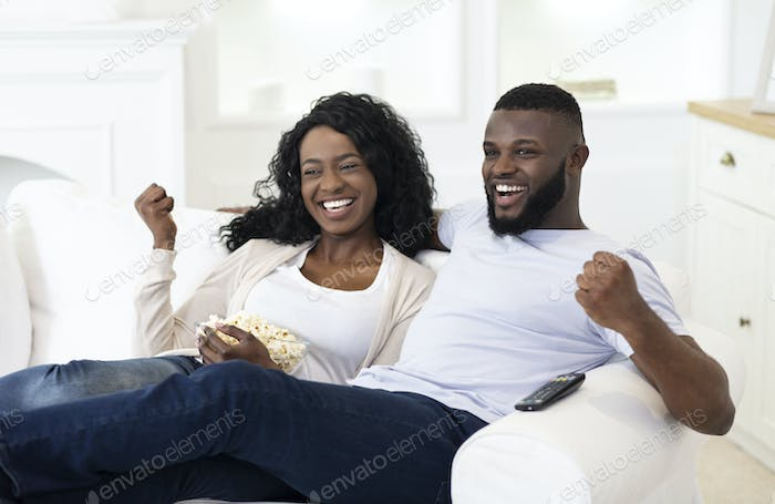 Married couple watching sport on tv, supporting their favorite team