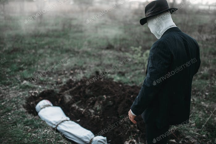 Bloody murderer stands against a grave with victim