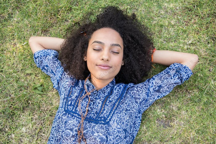 Pretty young woman napping in park on a summers day