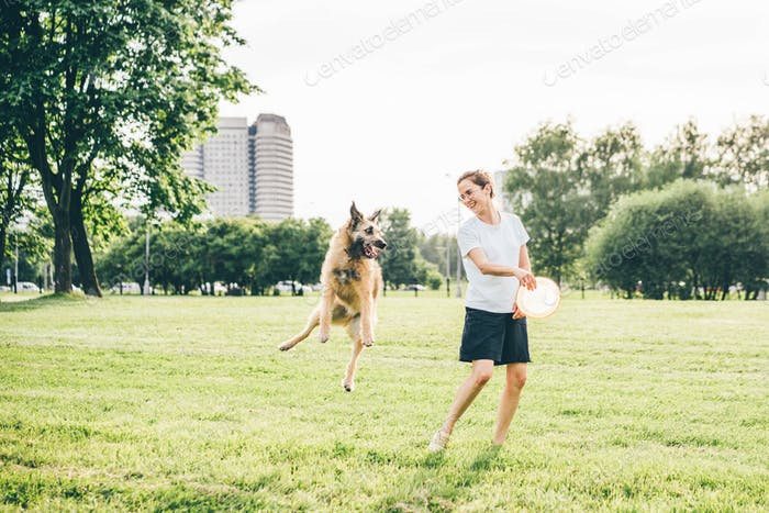 lady with glasses in white t-shirt plays with jumping funny grey fluffy dog