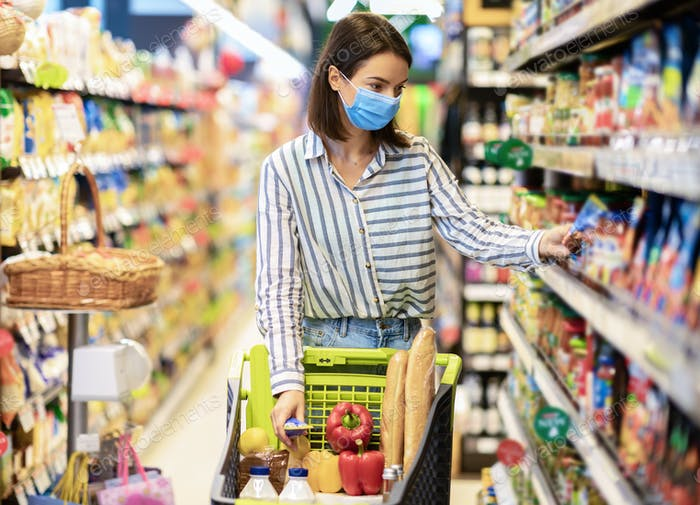 Young woman in mask with trolley cart shopping in hypermarket