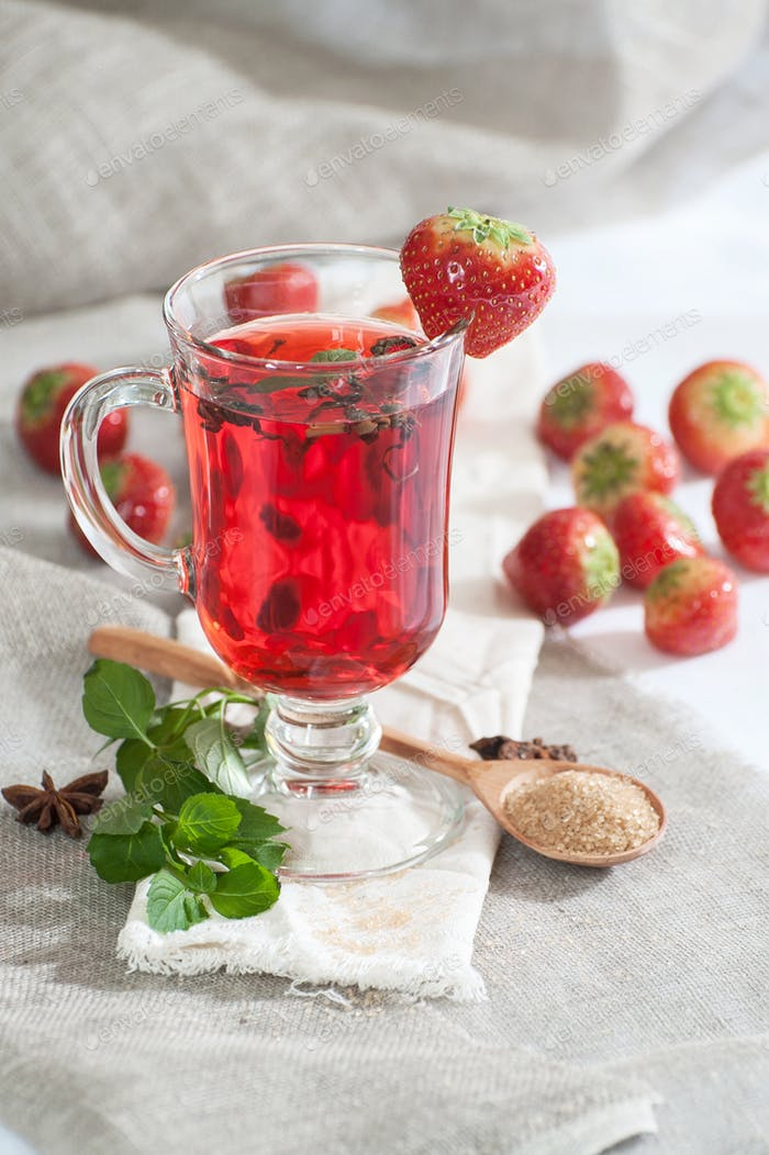 Hot strawberry drink with fresh mint in a glass cup.
