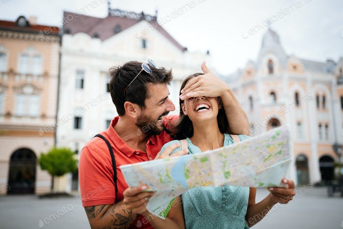 Happy young couple walking outdoors sightseeing and holding a map