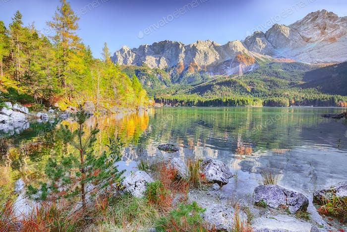 Faboulus autumn landscape of Eibsee Lake in front of Zugspitze summit under sunlight
