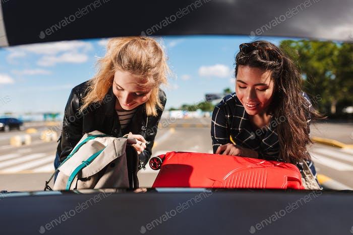 Zwei hübsche lächelnde Mädchen glücklich zusammenfalten Koffer zusammen in