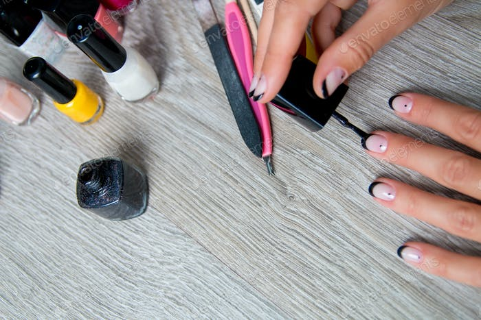 Schwarzer Nagellack wird auf der Hand mit Werkzeugen für die Maniküre auf dem Hintergrund aufgetragen.