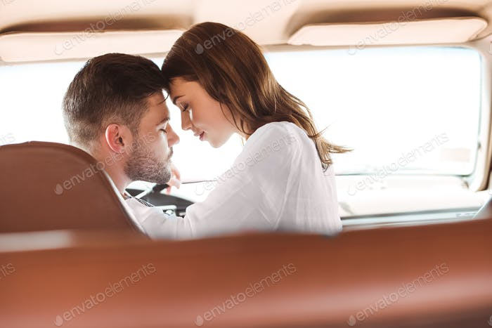 beautiful couple with closed eyes going to kiss in car together