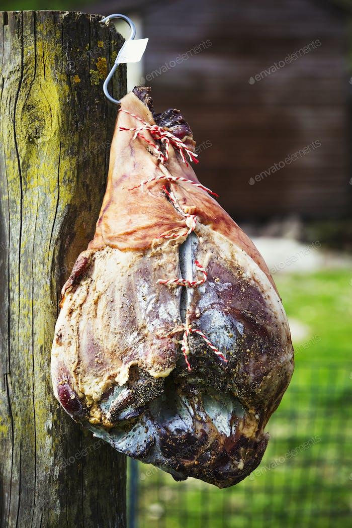 Nahaufnahme eines ausgehärteten Schinkens, der an einem Holzzaun hängt.