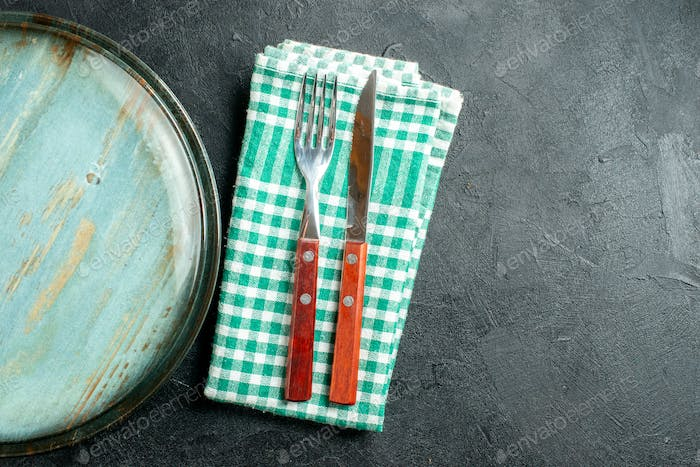 top half view round platter knife and fork on green and white checkered napkin on black background