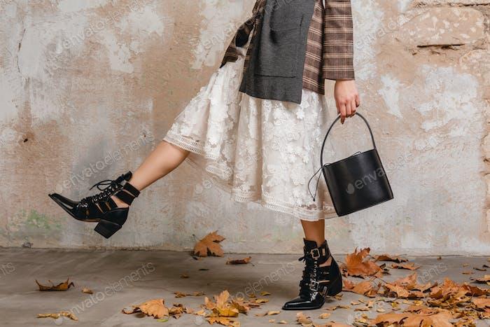 Nahaufnahme der Beine in Stiefeln einer stilvollen Frau im Jackenmantel, Schuhzubehör