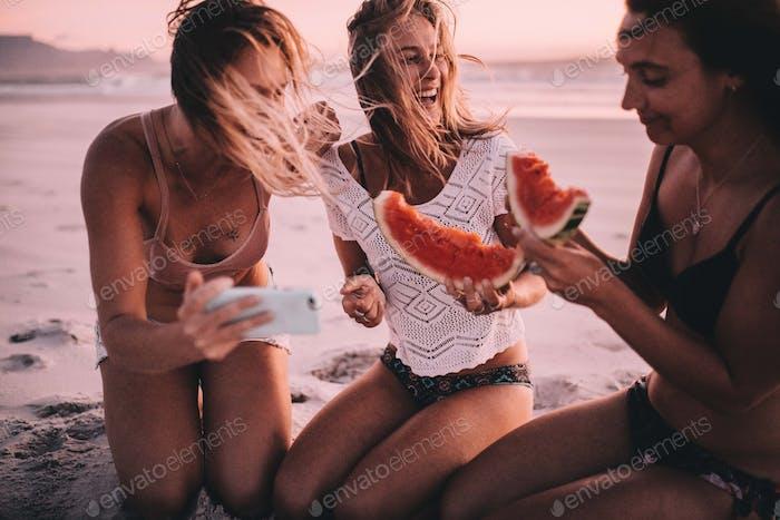 Mujeres caucásicas amigas comiendo sandía en la playa