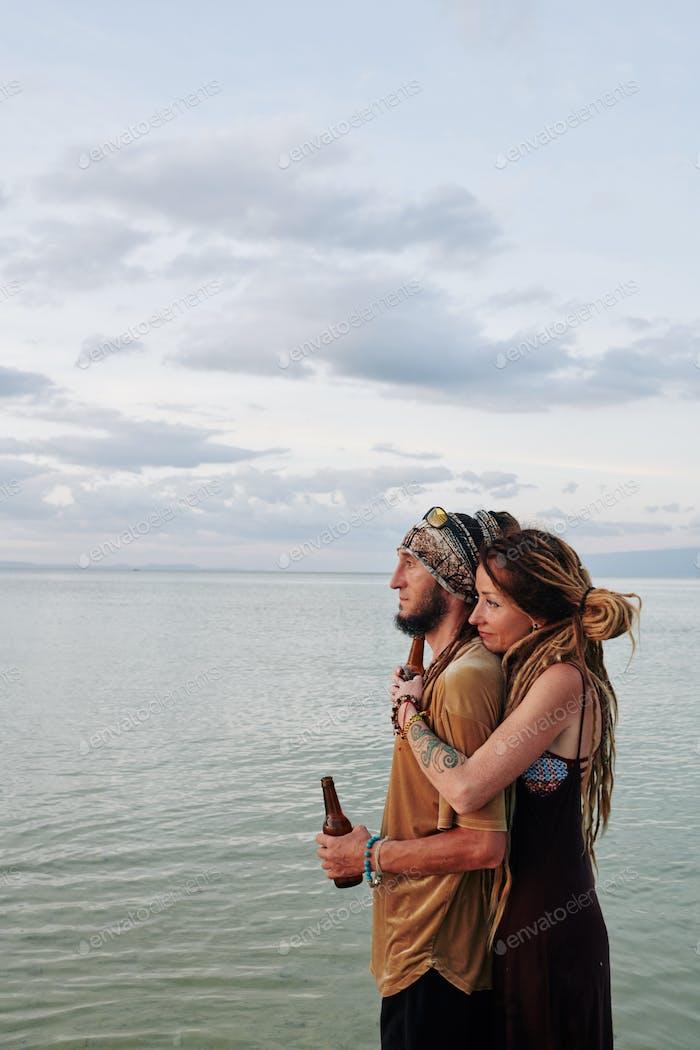 Sad couple looking at seascape