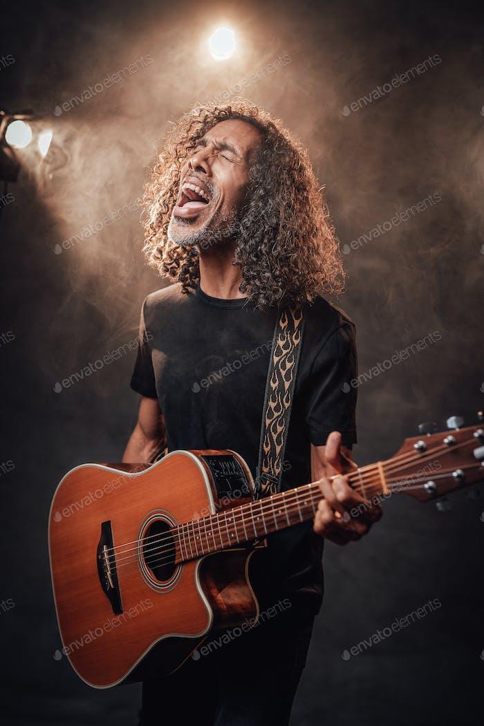 Hispanischer Musiker singt emotional und spielt Gitarre in Bühnenlichtern, umgeben von Rauch